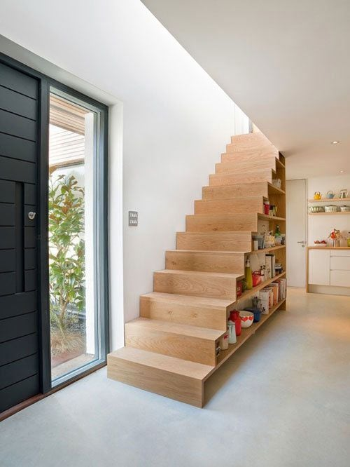 wooden stairs with bookshelves underneath